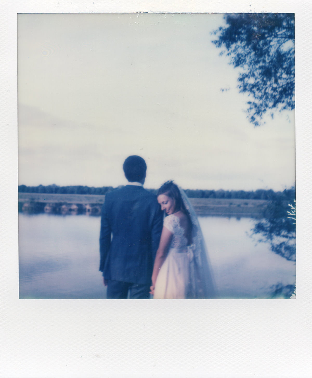 Impossible Project film photo of Bride in Claire Pettibone dress and veil with groom in Savile Row suit outside The Perch Oxford during wedding