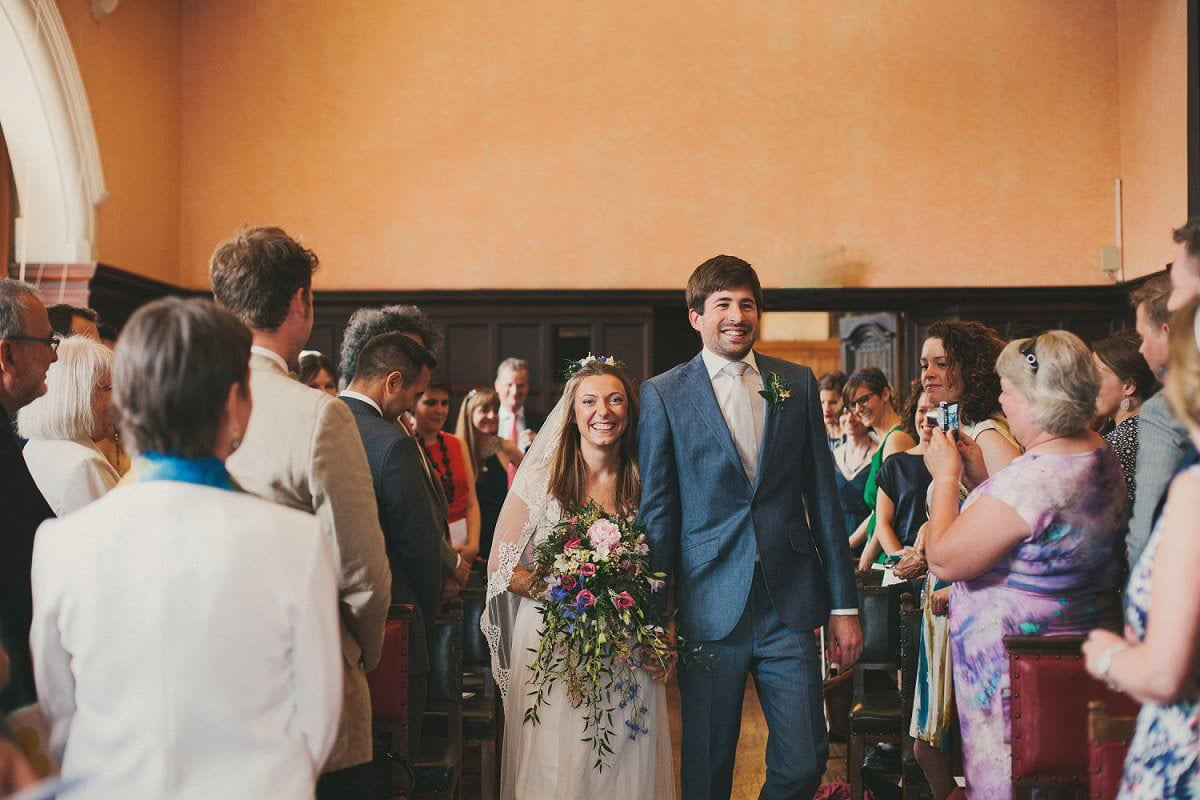 Bride in Claire Pettibone dress and veil with groom in blue Saville Row suit walking together down aisle at wedding in Oxford Town Hall
