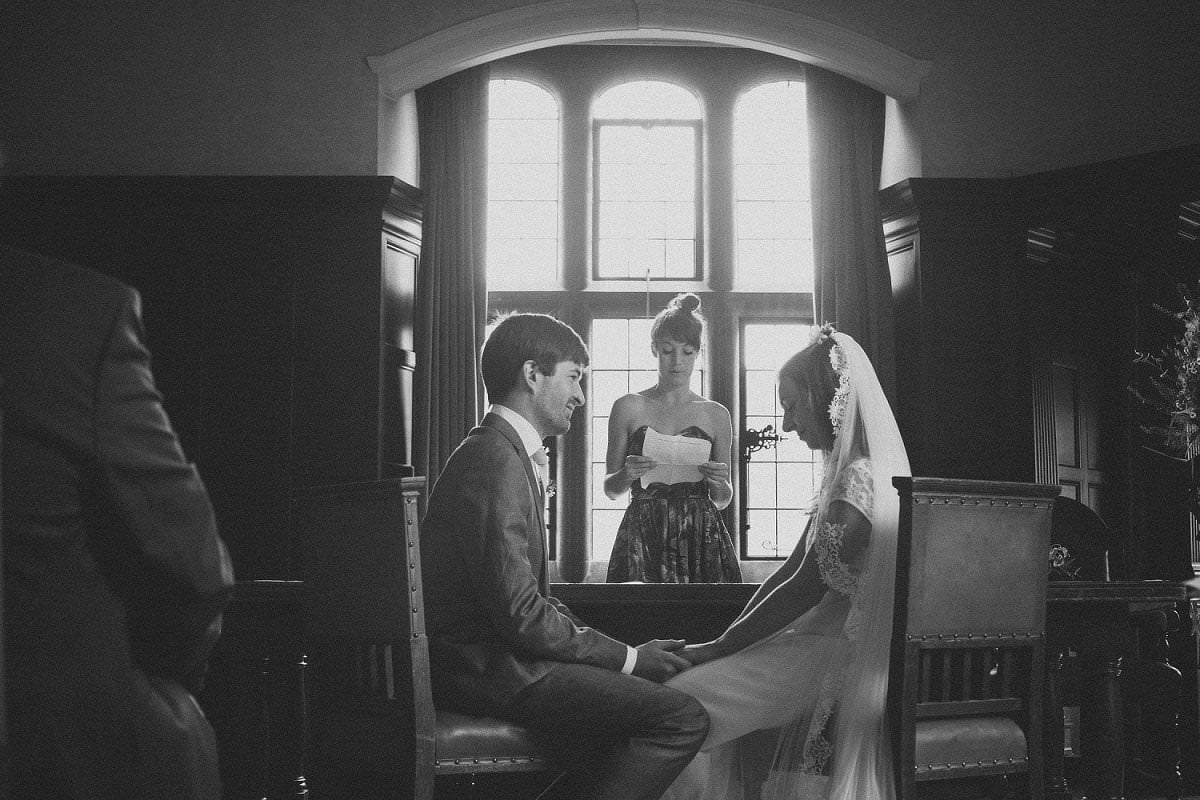 Bride and groom hold hands during wedding reading at Oxford Town Hall