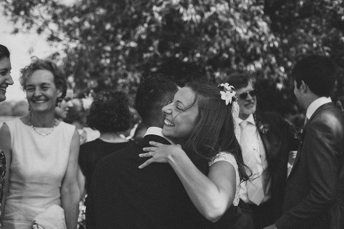 Bride hugging wedding guest in Port Meadow in Oxford