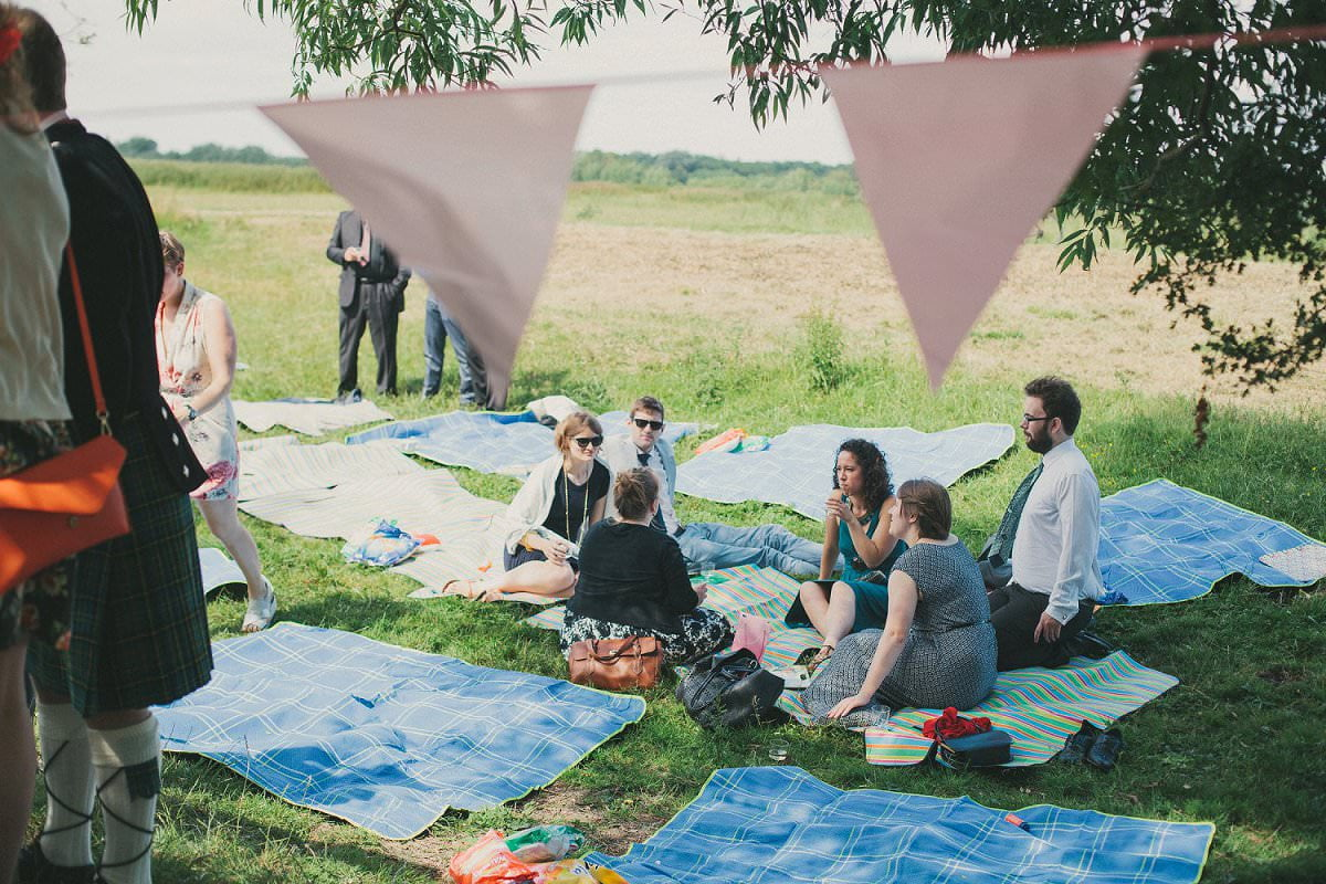 Wedding guests relaxing on picnic blankets during drinks reception in Port Meadow in Oxford