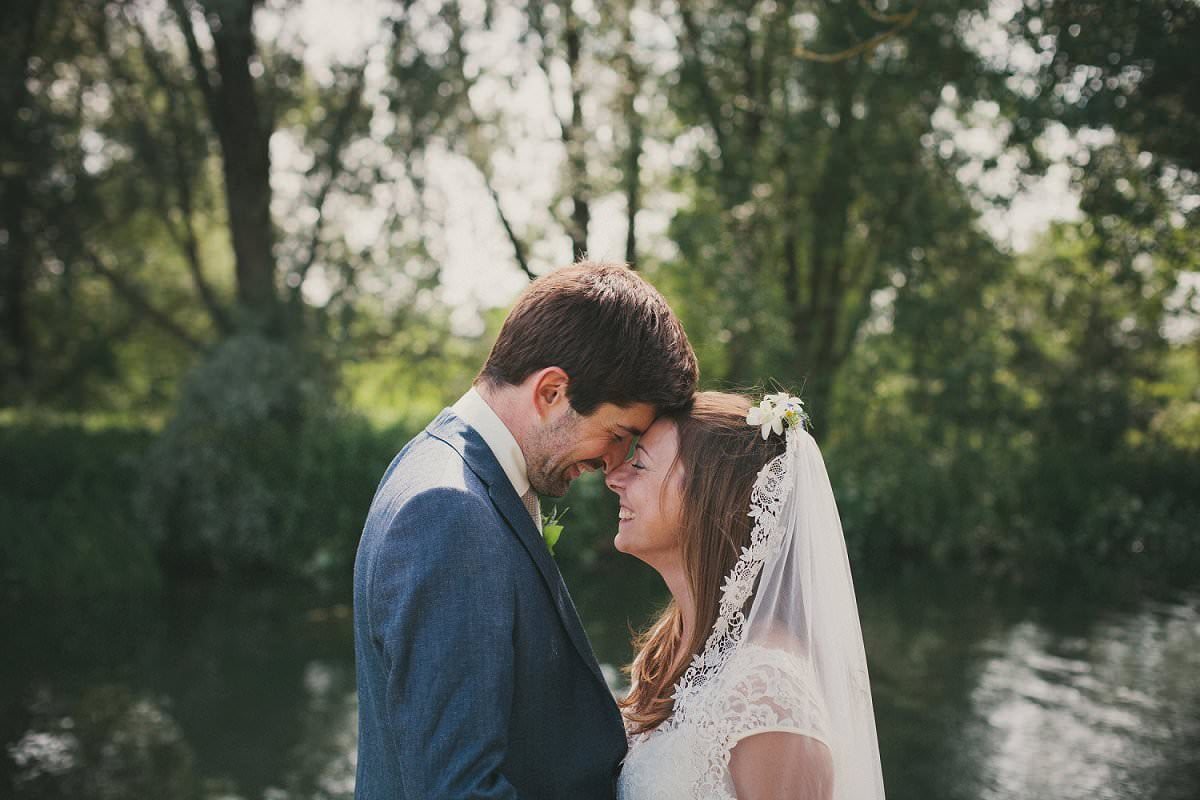 Bride in Claire Pettibone dress and veil rubs nose with groom in blue Saville Row suit during wedding at Port Meadow Oxford