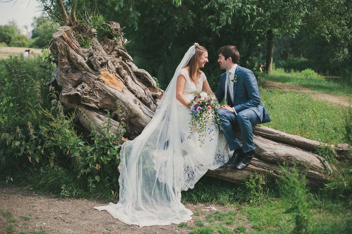 Bride in Claire Pettibone dress and veil sits on fallen tree with groom in blue Saville Row suit during wedding at Port Meadow Oxford