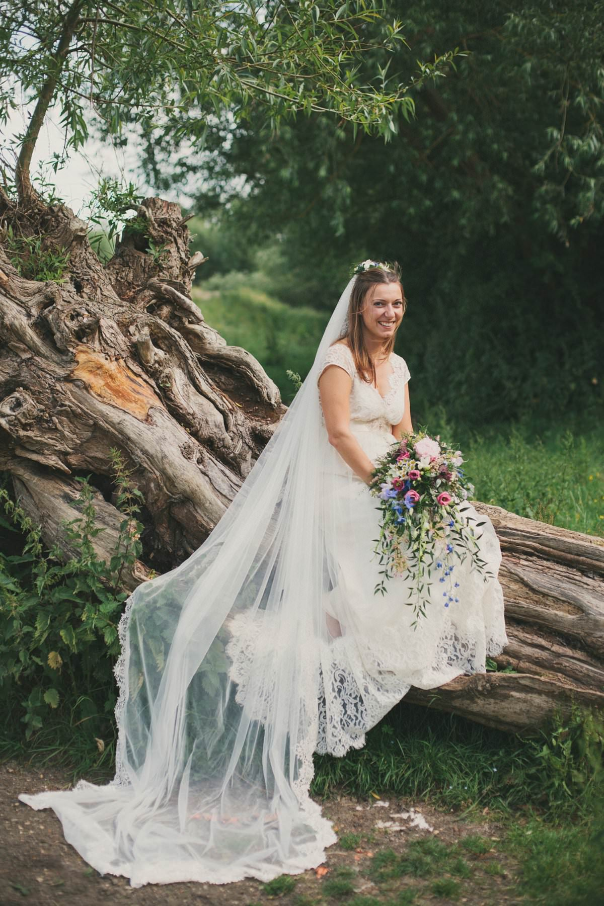 Bride in Claire Pettibone dress and veil with bouquet sits on fallen tree during wedding at Port Meadow Oxford