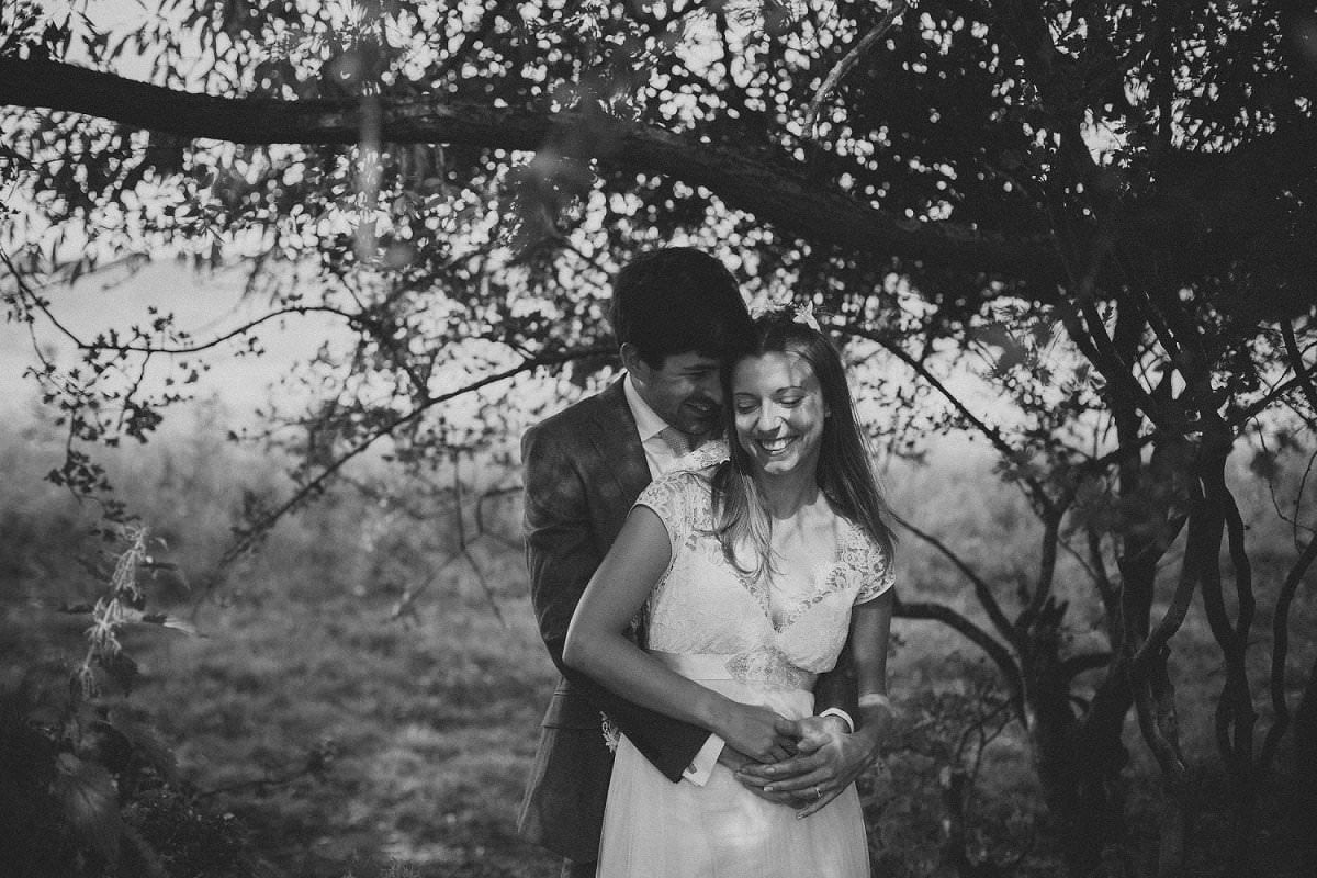 Bride in Claire Pettibone dress is held by groom under tree during wedding at Port Meadow Oxford