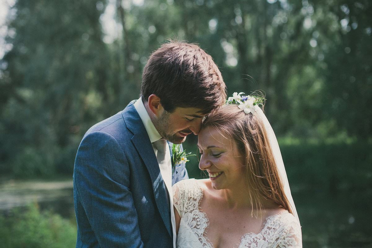 Bride in Claire Pettibone dress and groom in blue Saville Row suit share happy moment during wedding at Port Meadow Oxford