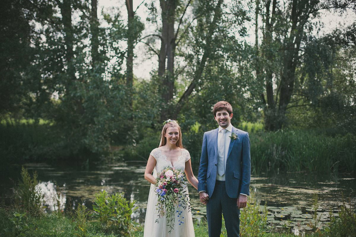 Bride in Claire Pettibone dress and groom in blue Saville Row suit hold hands by pond during wedding at Port Meadow Oxford