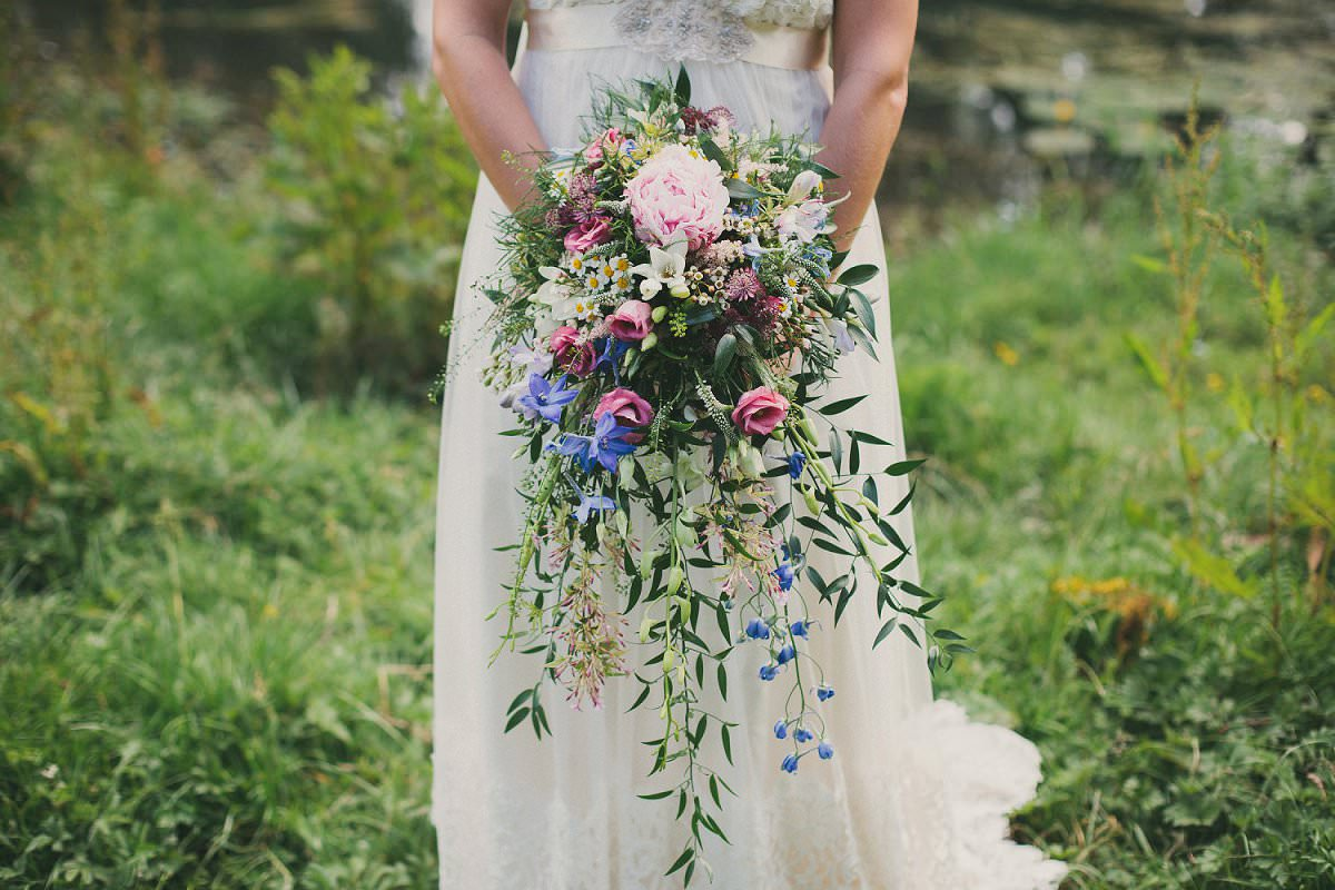 Bride in Claire Pettibone dress holds wild bouquet during wedding at Port Meadow Oxford