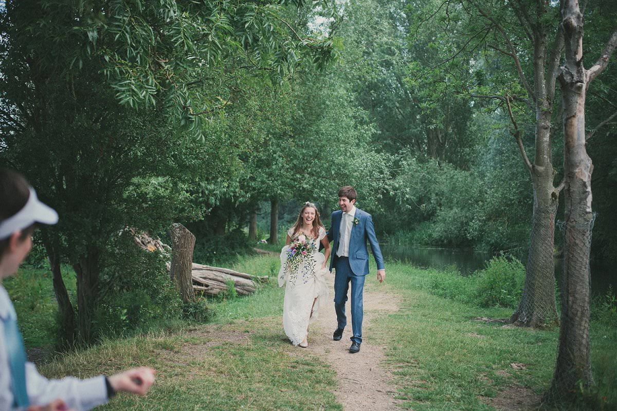 Bride in Claire Pettibone dress and groom in blue Saville Row suit walking together during wedding in Port Meadow Oxford