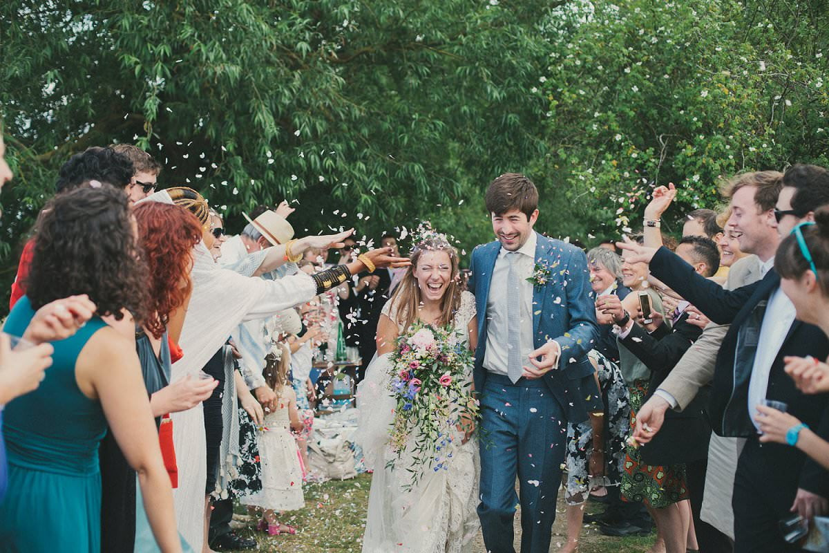 Bride in Claire Pettibone dress and groom in blue Savile Row suit get confetti thrown on them at wedding in Port Meadow Oxford