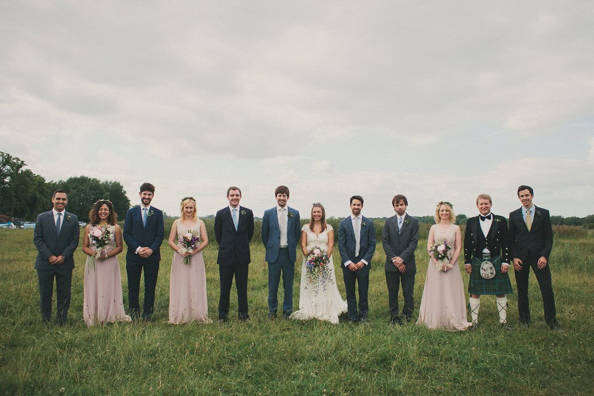 Bride in Claire Pettibone dress and groom in blue Savile Row suit with bridesmaids and groomsmen at wedding in Port Meadow Oxford