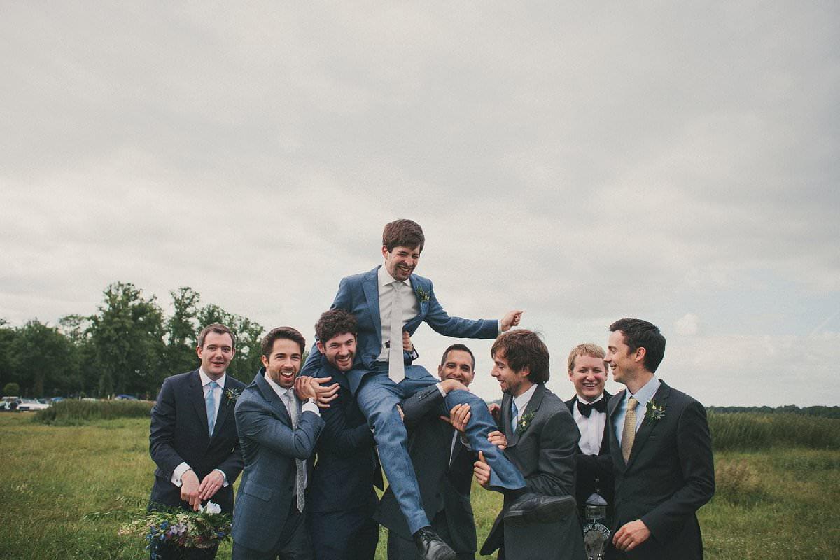 Groomsmen pick up groom in blue Savile Row suit at wedding in Port Meadow Oxford
