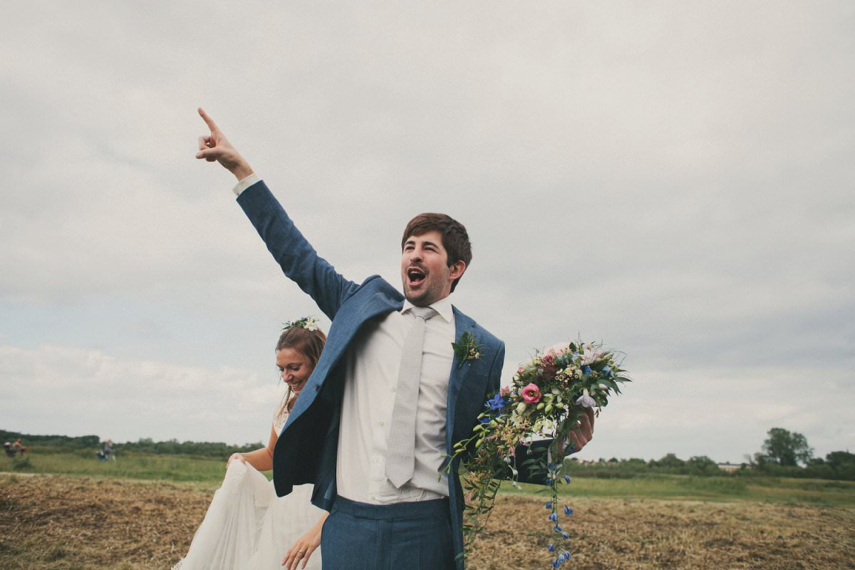 Groom in blue Savile Row suit directs guests to next venue at wedding in Port Meadow Oxford
