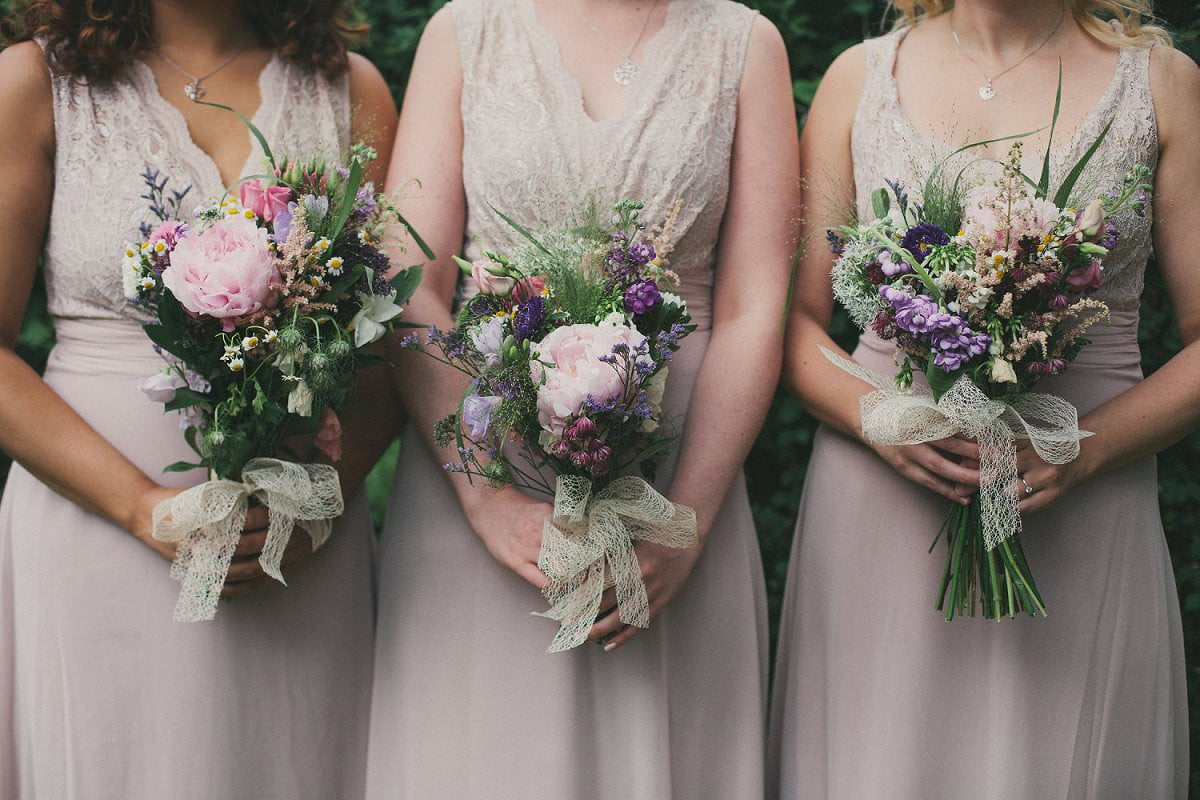 Bridesmaids in lilac lace dresses with wildflower bouquets with lace at wedding at The Perch Oxford