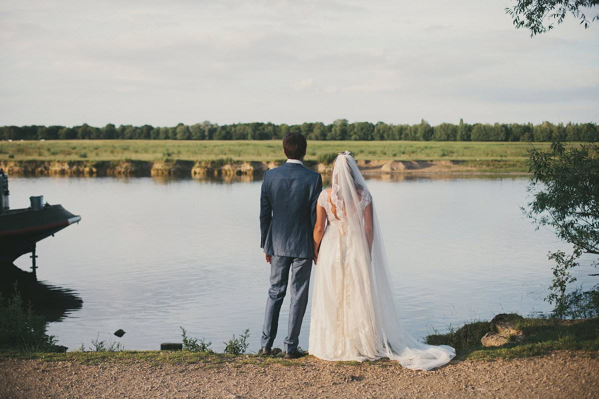 Bride in Claire Pettibone dress and veil with groom in Savile Row suit look at water outside The Perch Oxford during wedding