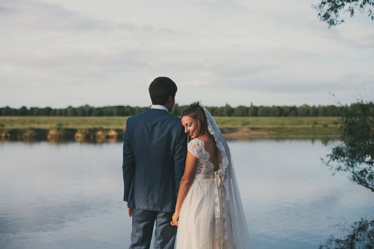 Bride in Claire Pettibone dress and veil with groom in Savile Row suit by water outside The Perch Oxford during wedding