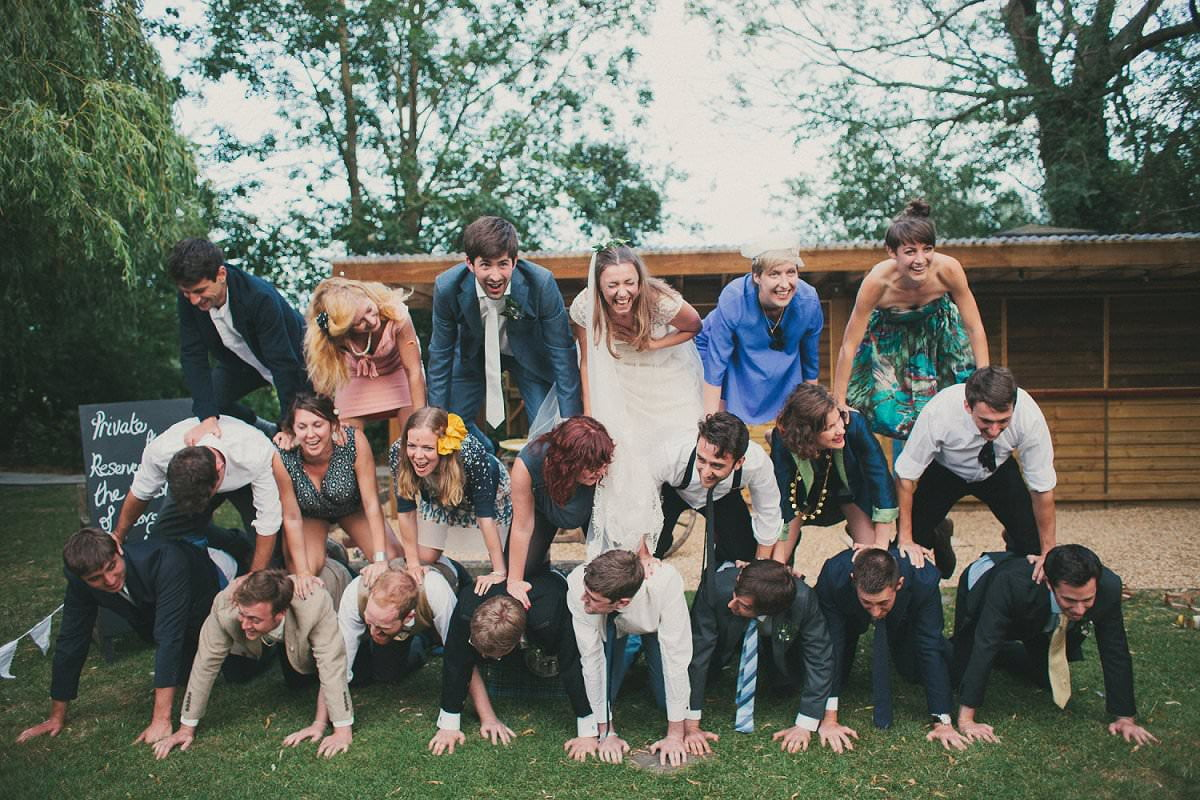 Bride in Claire Pettibone dress and groom in blue Savile Row suit create human pyramid with guests during wedding at The Perch Oxford