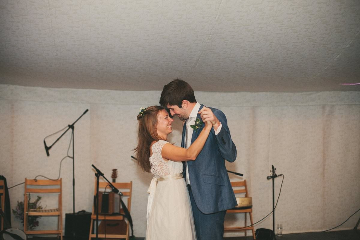 Bride in Claire Pettibone dress and groom in blue Savile Row suit share first dance during wedding at The Perch Oxford