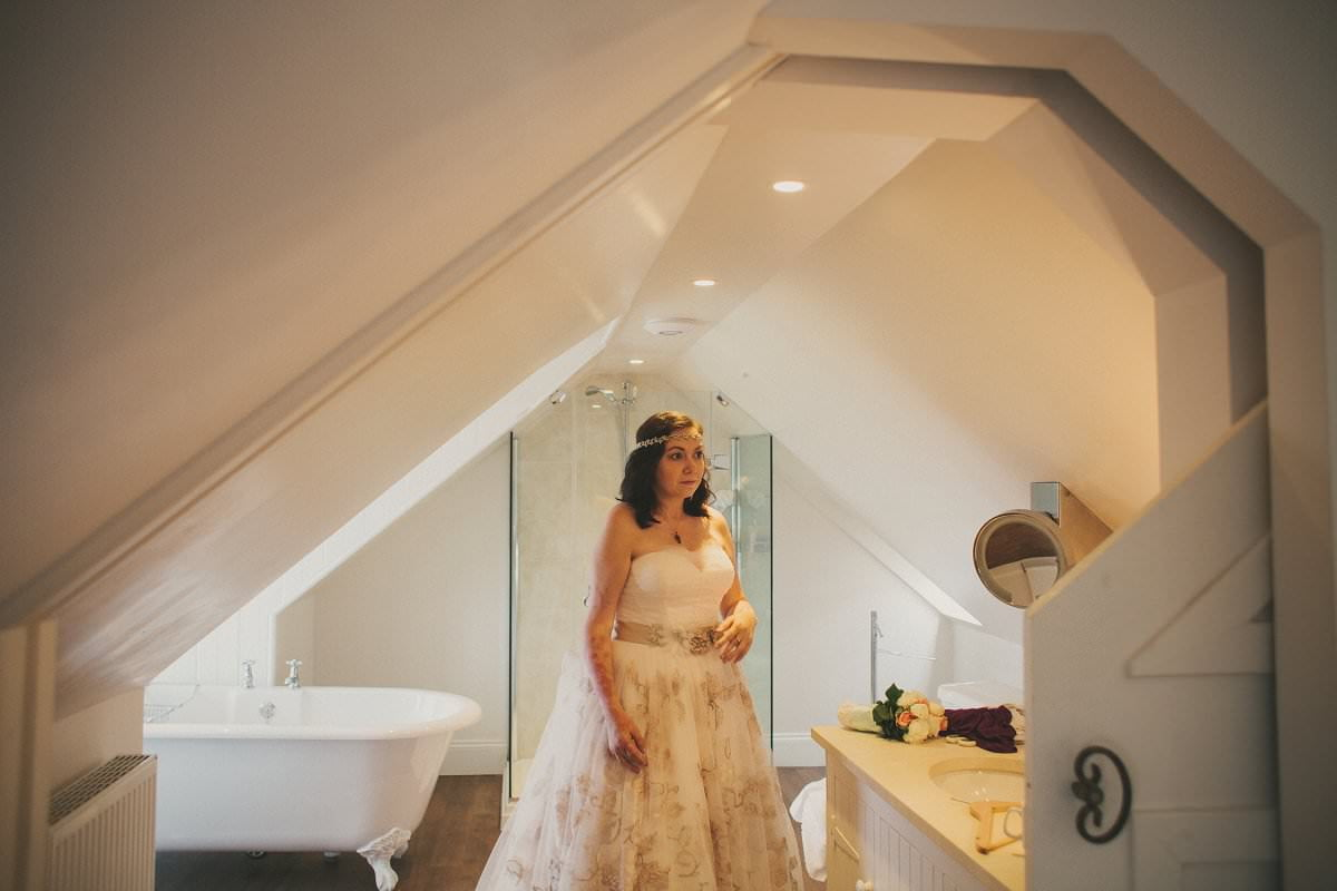 Bride stands in bathroom while getting ready for wedding elopement at Glenisle Hotel on The Isle of Arran Scotland