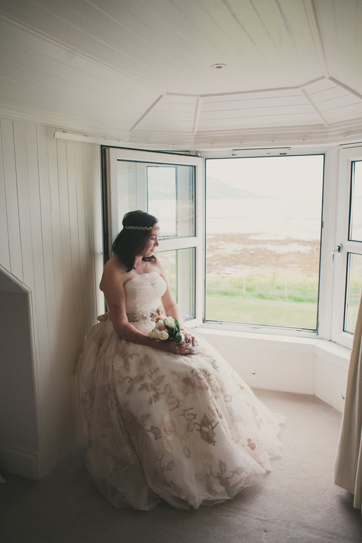 Bride sits by window at wedding elopement at Glenisle Hotel on The Isle of Arran Scotland