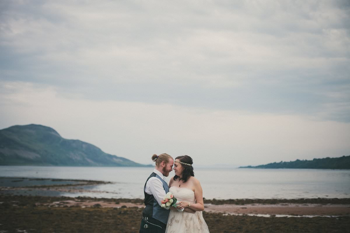 Bride and groom during first look by water at wedding elopement outside Glenisle Hotel on The Isle of Arran Scotland