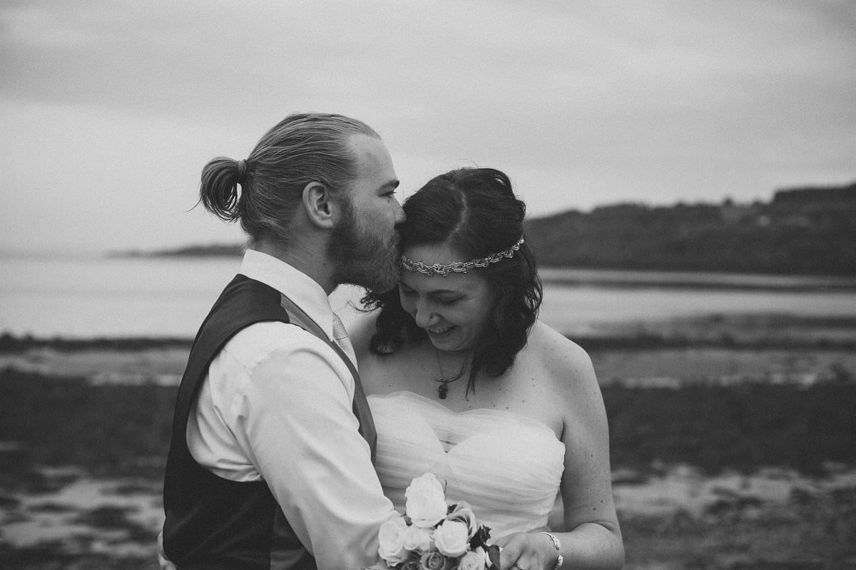 Groom kisses bride's forehead during first look at wedding elopement outside Glenisle Hotel on The Isle of Arran Scotland