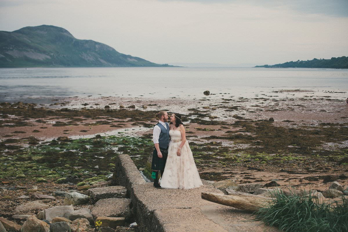 Bride and groom by sea during first look at wedding elopement outside Glenisle Hotel on The Isle of Arran Scotland