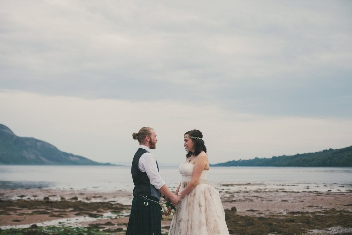 Bride and groom hold hands by sea during first look at wedding elopement outside Glenisle Hotel on The Isle of Arran Scotland