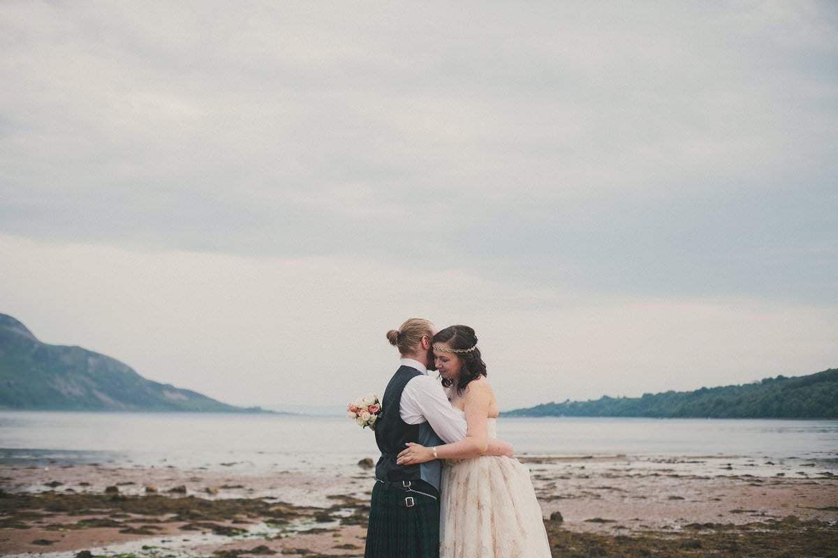 Bride and groom hug by sea during first look at wedding elopement outside Glenisle Hotel on The Isle of Arran Scotland
