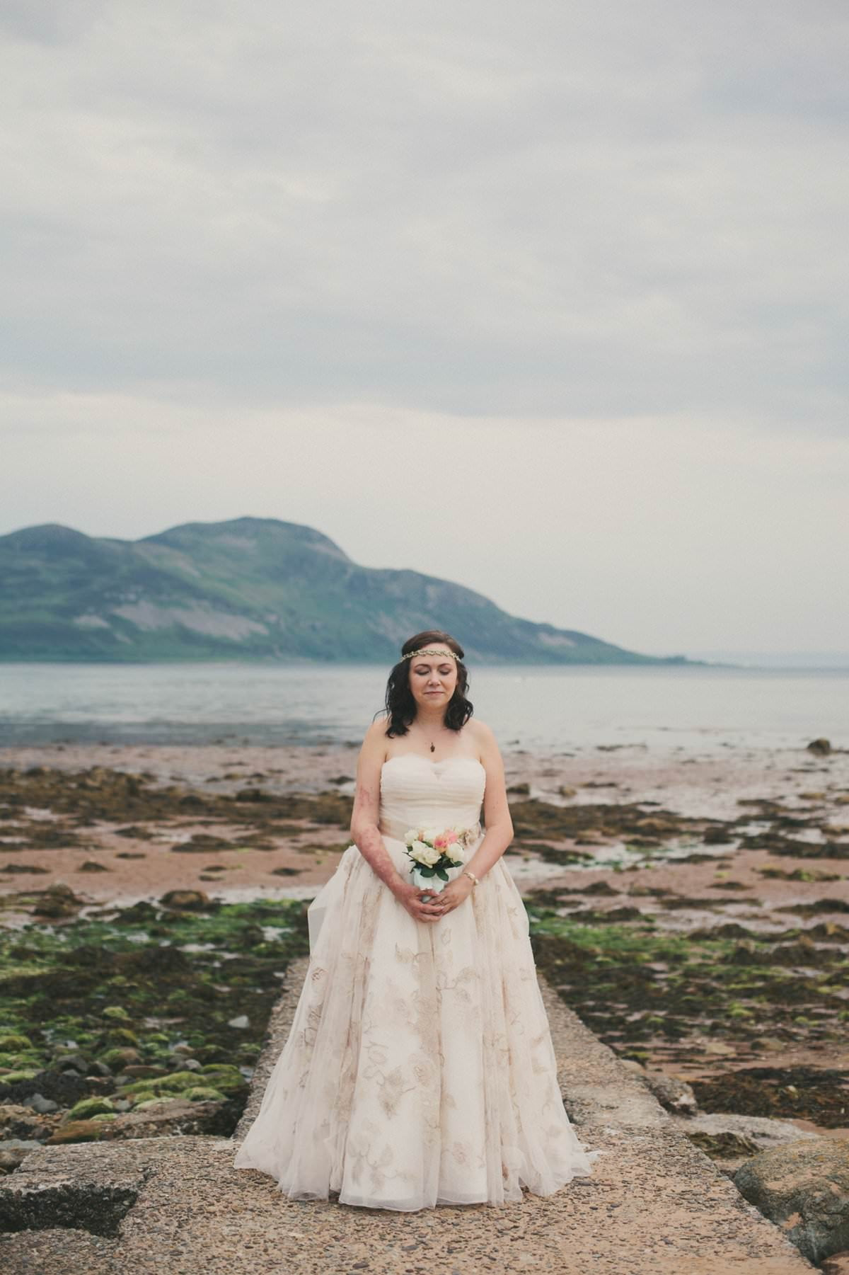 Bride holds bouquet by sea at wedding elopement outside Glenisle Hotel on The Isle of Arran Scotland