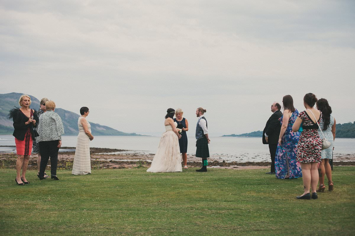 Bride and groom marry by sea outside Glenisle Hotel at wedding elopement on The Isle of Arran Scotland