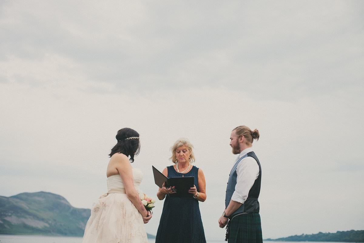 Bride and groom marry by sea during humanist ceremony outside Glenisle Hotel at wedding elopement on The Isle of Arran Scotland