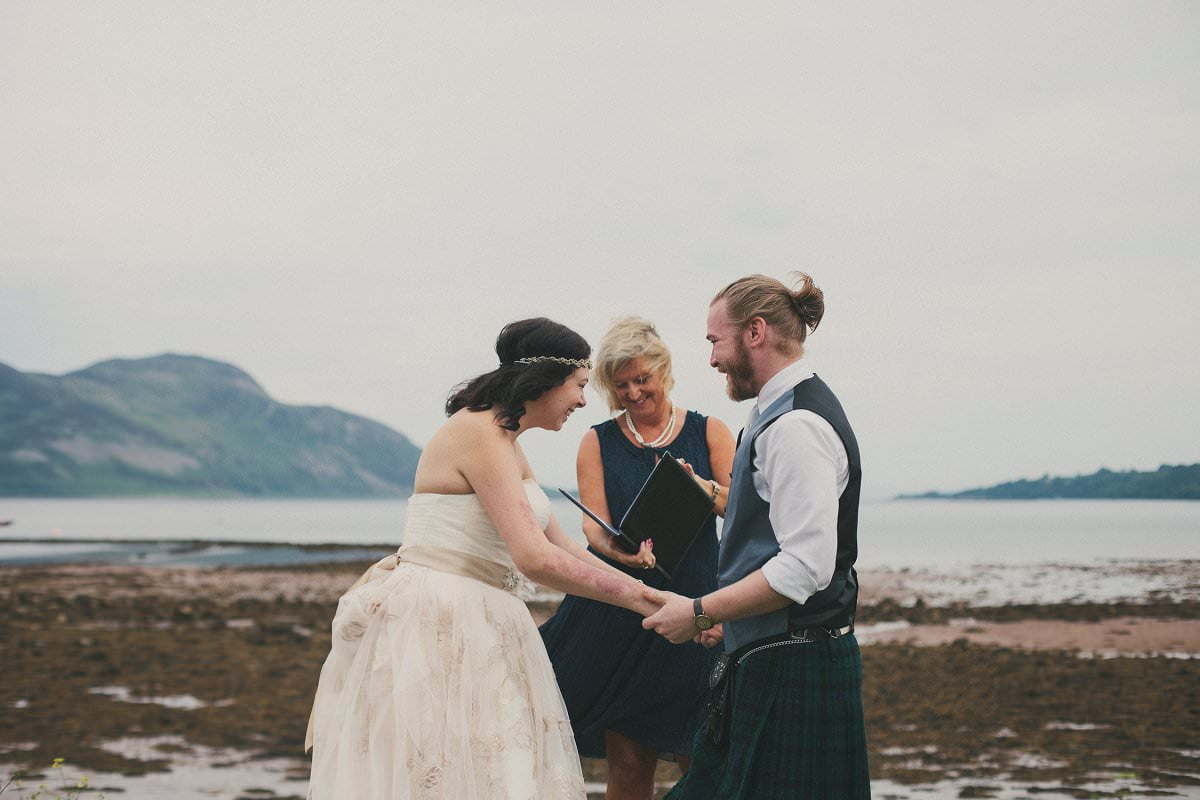 Bride and groom hold hands excitedly during humanist elopement wedding ceremony by Glenisle Hotel in Lamlash on The Isle of Arran Scotland