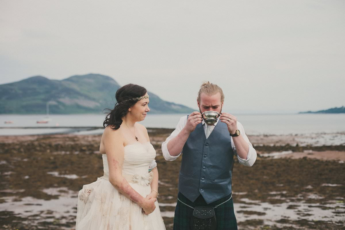 Bride and groom drink from quaichs during humanist elopement wedding ceremony by Glenisle Hotel in Lamlash on The Isle of Arran Scotland