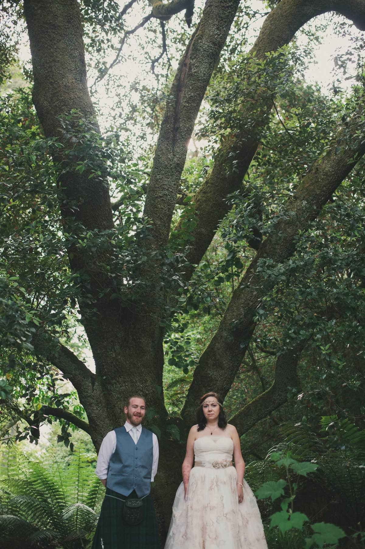 Bride and groom by tree in Brodick Castle gardens on The Isle of Arran Scotland during elopement wedding
