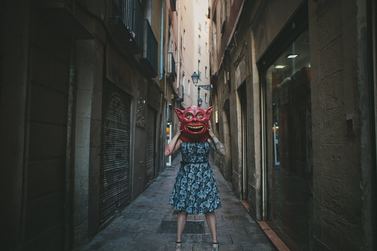 Portrait of woman standing in Barcelona Gothic Quarter street wearing mask photography
