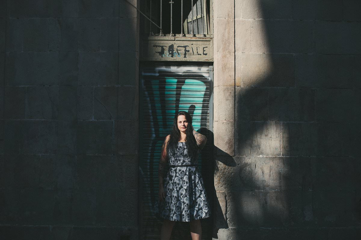 Portrait photography of woman standing in spill of light in Barcelona Gothic Quarter