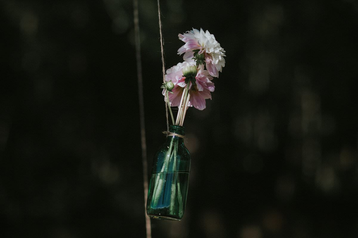 flower in glass bottle hanging from tree